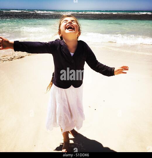 Smiling child running on a white sandy beach - Stock-Bilder