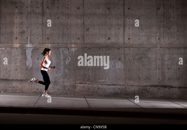 Woman running in industrial area - Stock Image