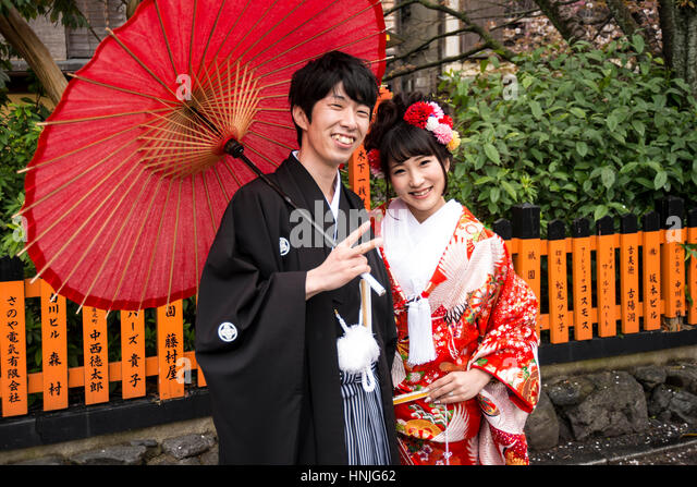 Newly weded young couple in traditional Japanese wedding attire posing for camera, Kyoto, Japan - Stock Image