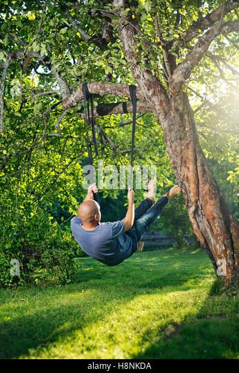 Man swinging on tree swing - Stock Image