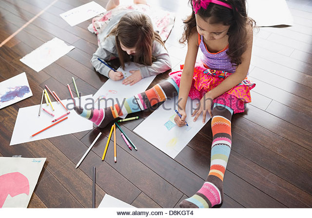 High angle view of girls coloring at home - Stock Image