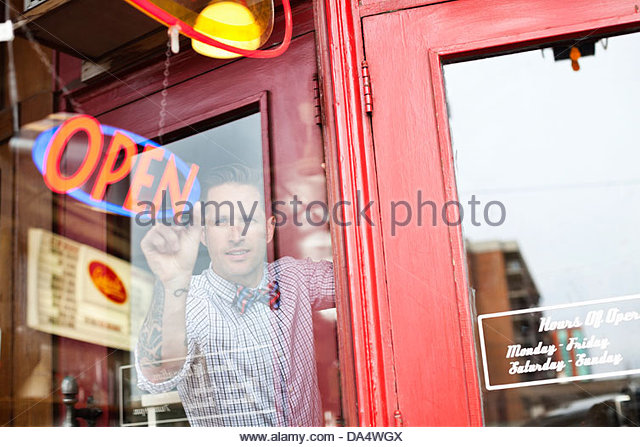 Male business owner adjusting open sign in diner window - Stock-Bilder