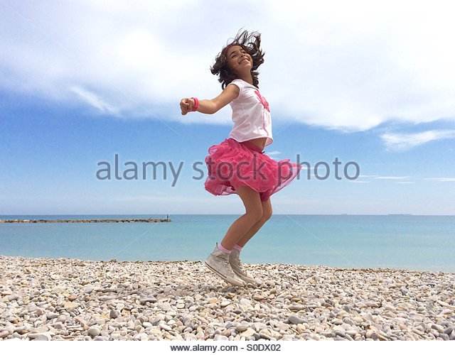 Girl in pink skirt enjoying spring weather in Benicassim (Spain) - Stock-Bilder