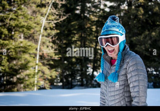 Woman in Toque and Ski Goggles Laughs at Camera in winter forest - Stock Image