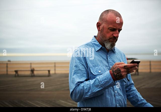 Man using smartphone at seaside - Stock Image