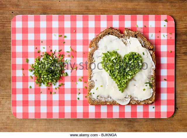 Buttered wholemeal bread with a heart of chives - Stock Image