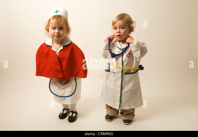 A young blonde girls dressed as a nurse standing beside a young blonde boy dressed as a doctor - Stock Image