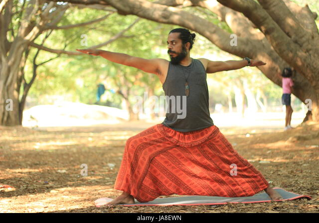 Young man performing the warrior II pose. Veerabhadrasana. Location - Cubbon Park, Bangalore. - Stock Image