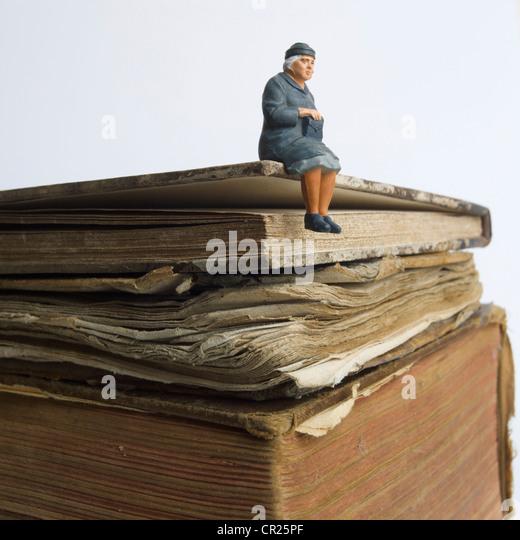 Elderly lady, miniature figurine, sitting on an old book - knowledge / wisdom / life history concept. - Stock Image