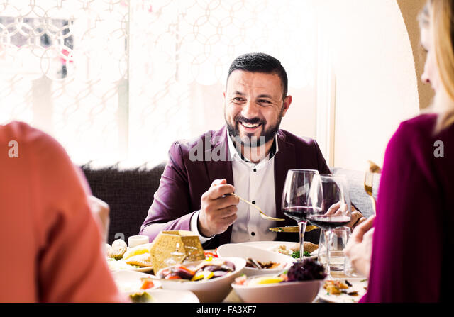 Happy man having meze with friends at Lebanese restaurant - Stock-Bilder