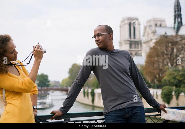 African woman taking photograph of boyfriend - Stock-Bilder