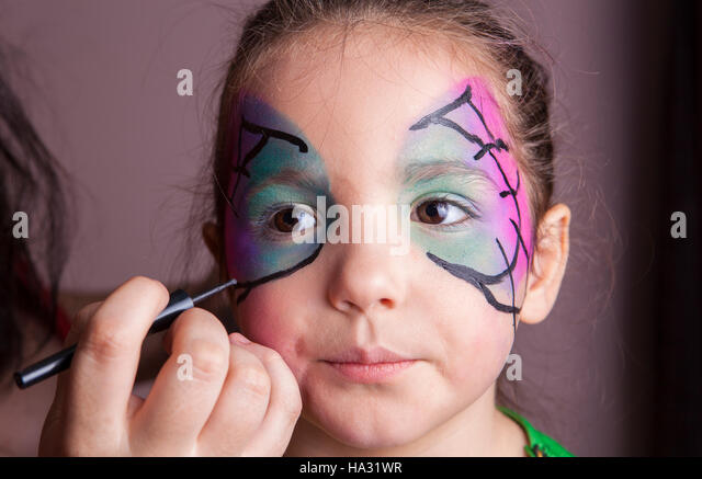Make-up artist working with a little girl before halloween party. She is applying black lines - Stock Image