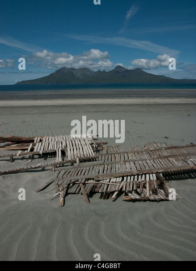 The Bay of Laig on the Isle of Eigg, with the Isle of Rum in the background. Wood collected for a bonfire. - Stock Image
