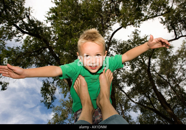 Young boy balanced on feet with arms out - Stock-Bilder