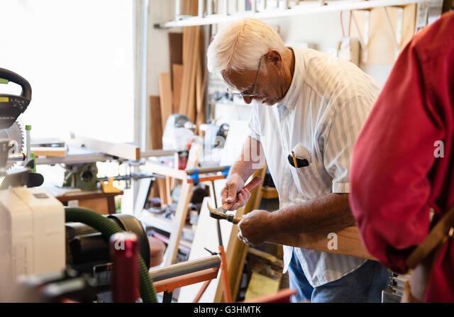 Senior man hammering woodblock in carpentry workshop - Stock Image
