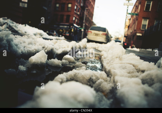 Snow turning to slush on road - Stock Image