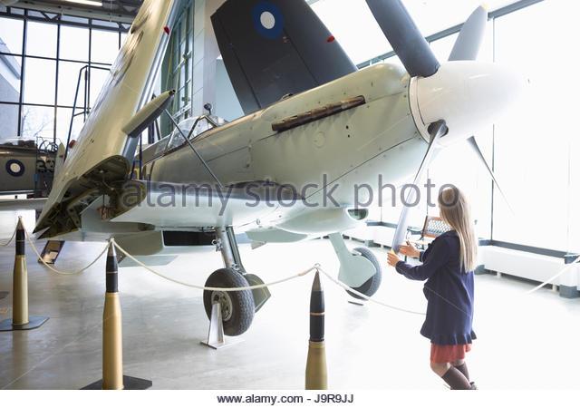 Curious girl touching propellor on airplane in war museum hangar - Stock-Bilder