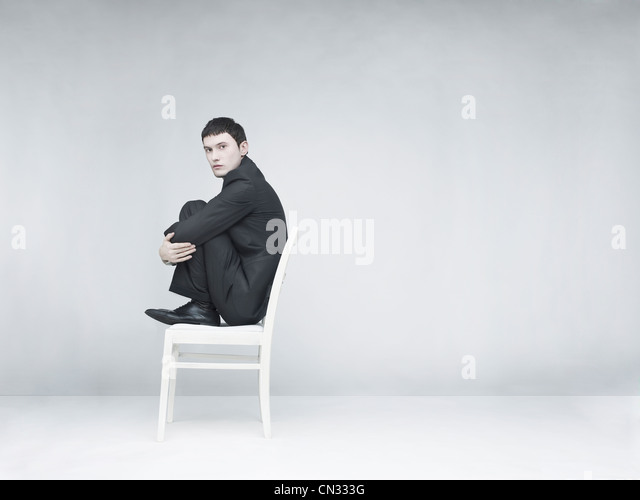 Surreal portrait of a man sitting on a white stool - Stock Image