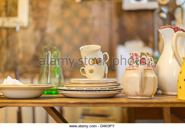 Decorative dishes piled on table - Stock Image