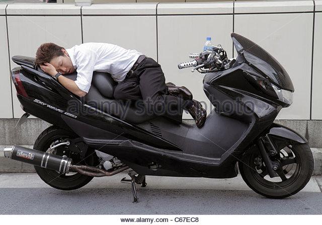 Japan Tokyo Ikebukuro Asian man sleeping catnapping motorcycle Suzuki Skywave - Stock Image