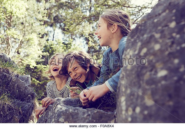 Three children sitting on rocks in forest, laughing - Stock Image