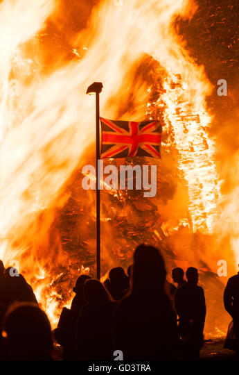 """Belfast, Northern Ireland. 11 Jul 2016 - A Union Flag flies in front of the traditional """"11th Night"""" bonfire - Stock Image"""