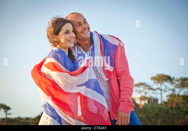 Couple wrapped in british flag on Bournemouth beach, Dorset, UK - Stock Image