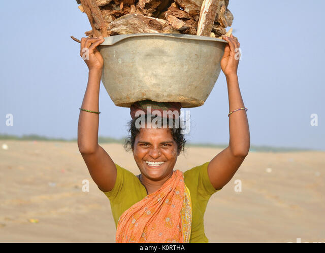 Middle-aged Orissan woman from the local fishing community at Puri, carrying a heavy load of firewood on her head. - Stock Image