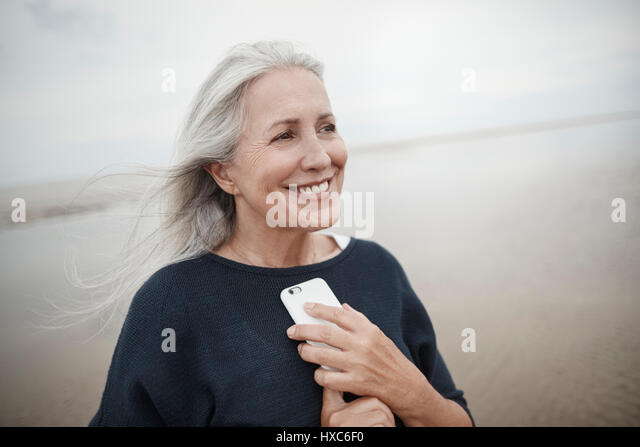 Smiling senior woman holding cell phone on winter beach - Stock Image