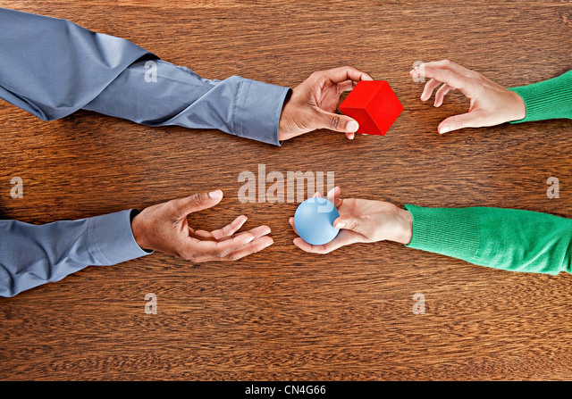 People exchanging colourful shapes - Stock Image