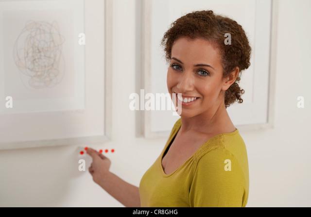 Art dealer placing sold dots under artwork in gallery - Stock Image