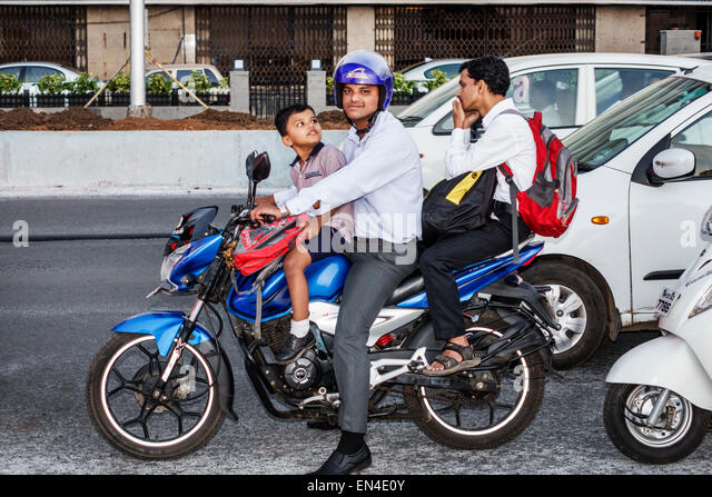 India Asian Mumbai Churchgate Marine Drive man father boy son riding motorcycle motor scooter traffic - Stock Image