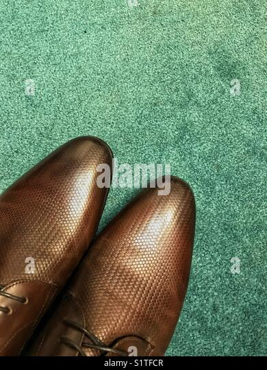 Pair of brand new brown men's shoes on green carpet. - Stock Image