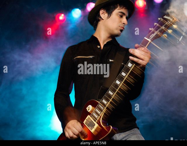 Rock Guitarist on stage in Concert, low angle view, front view - Stock Image