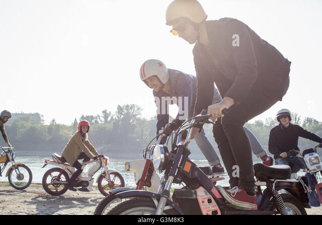 Group of friends riding mopeds beside lake, two men doing stunts - Stock Image