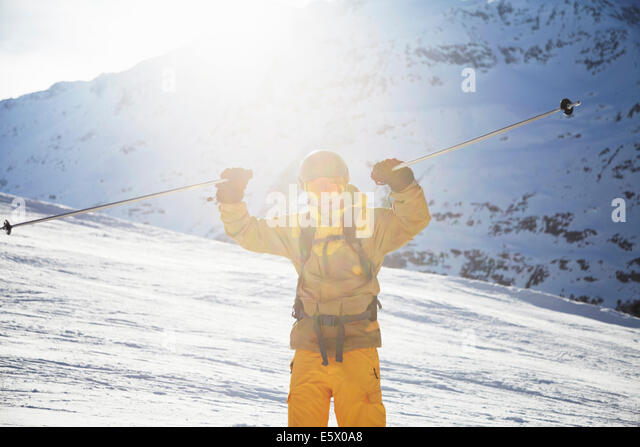 Mid adult male skier holding up ski poles in celebration, Austria - Stock Image