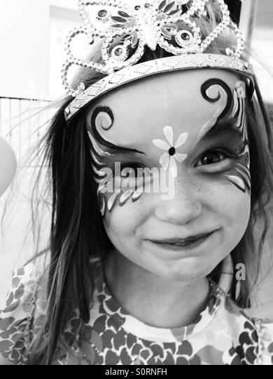 Girl with face paint and tiara - Stock Image