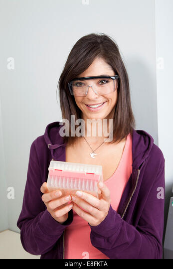 Woman holding container of sample tubes - Stock Image