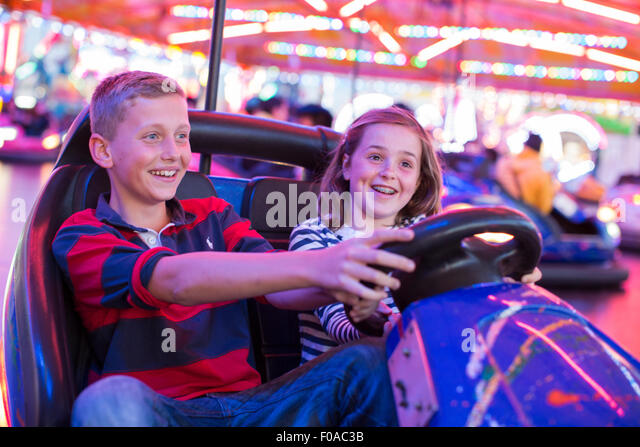 Brother and sister on fairground bumper cars - Stock Image