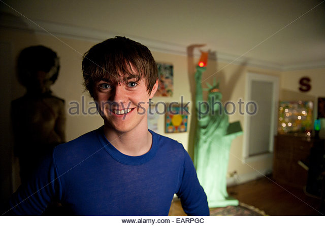 A teenage boy proudly shows off his bedroom. - Stock Image