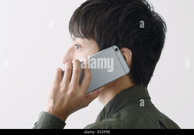 Young Japanese man on the phone - Stock Image
