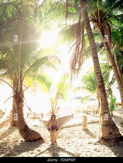A young Filipina woman relaxes in a hammock at sunrise. Boracay, Philippines. - Stock Image