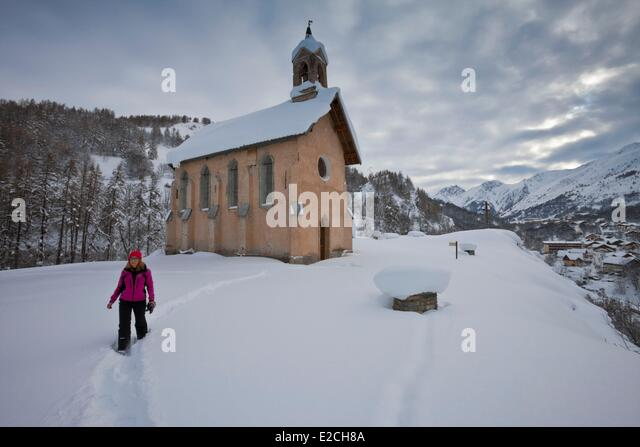 France, Savoie, Maurienne Valley, Valloire, the chapel of St Pierre, snowshoe hiker - Stock Image