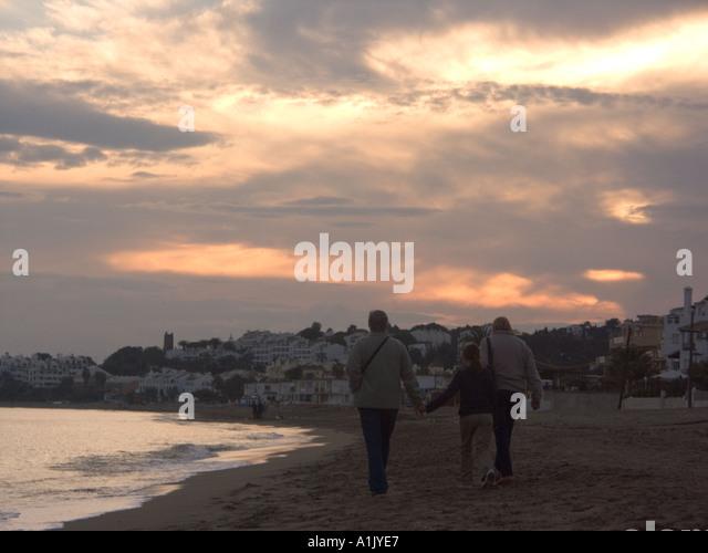 Family strolling at dusk, La Cala beach, Mijas Costa, Costa del Sol, Spain, Europe, - Stock Image