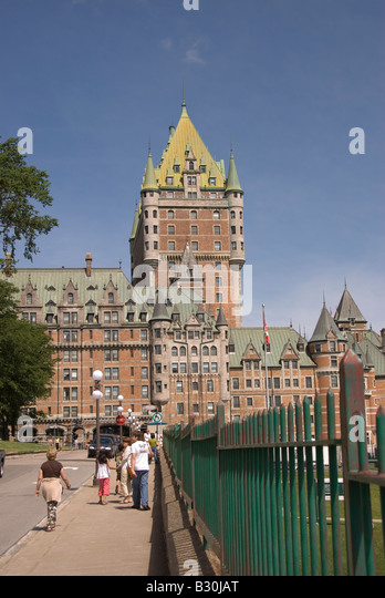 Tourists strolling sidewalk in front of Chateau Frontenac hotel old Quebec City canada - Stock Image