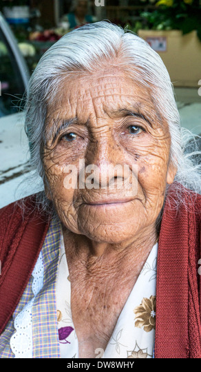 proud humble immaculate wrinkled 101 year old Mexican indigenous Indian woman vendor working at mercado La Merced - Stock Image