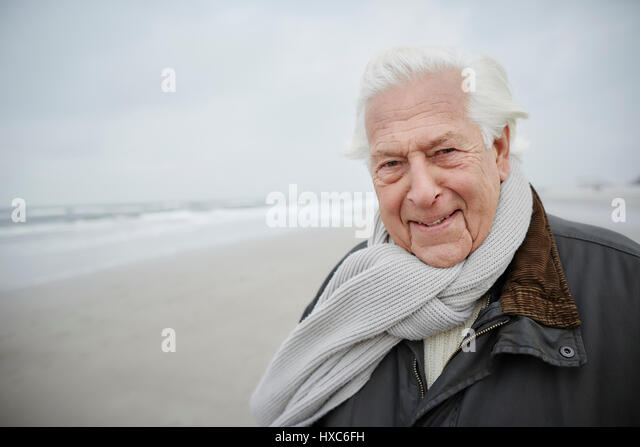 Portrait confident senior man wearing scarf on winter beach - Stock Image