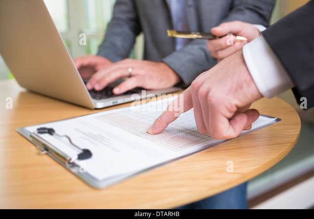 Closeup of Two hands businessmen working together in modern office with laptop - Stock Image