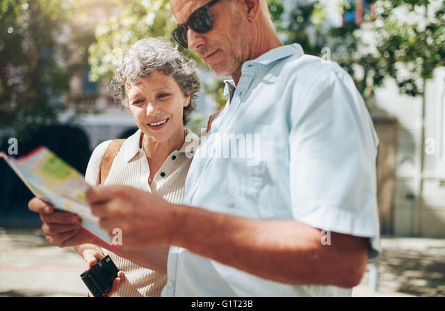 Close up shot of active senior on a vacation reading a city map. Mature man and woman using city map for directions - Stock Image