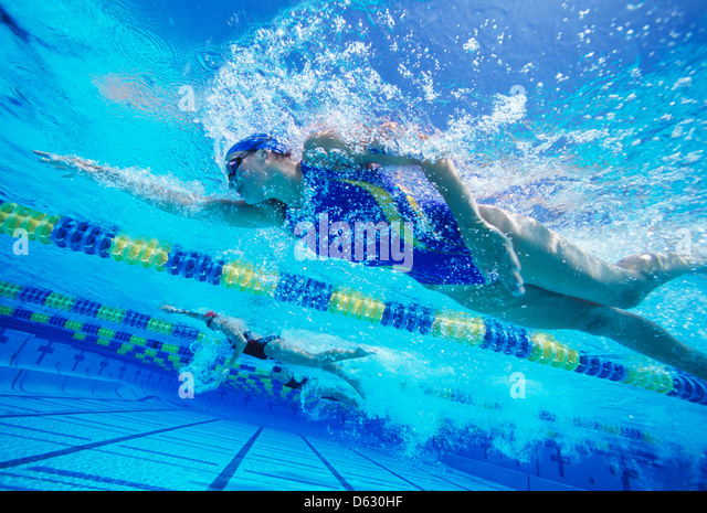 Female professional participants racing in pool - Stock Image